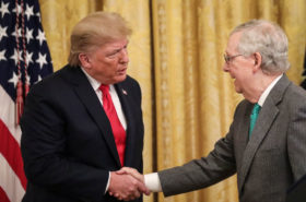 President Donald Trump, center, shakes hands with Senate Majority Leader Mitch McConnell, right.